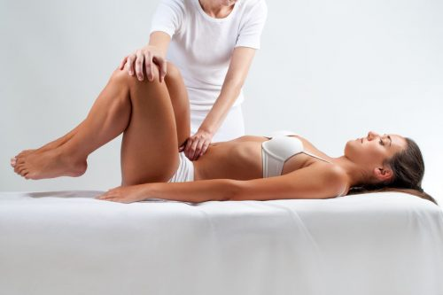 42304180 - close up full length portrait of woman at osteopathic session. therapist doing manipulative massage on belly.