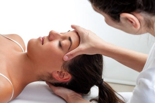 42304211 - close up of osteopath doing healing treatment on womans head. hands doing massage on front and back of head.